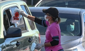 A Covid-19 testing site staff member gives a self-administered test kit to a person in their car at a drive-up testing site in Los Angeles.