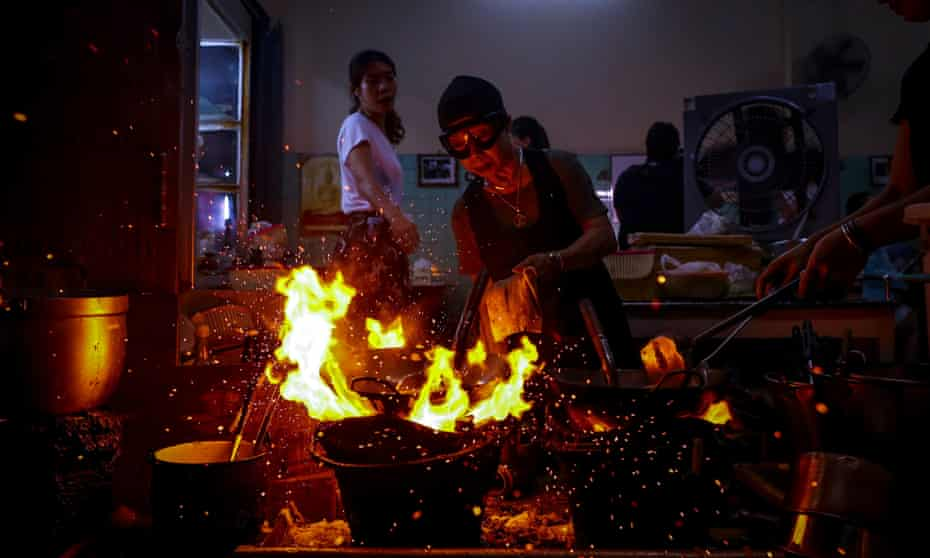 70-year-old chef Jay Fai (C) cooks on coal powered stoves at her Michelin star restaurant in Bangkok,