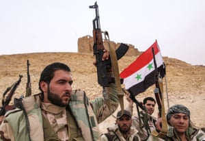 Syrian government army soldiers hold up a Syrian national flag near Fakhr al-Din al-Maani Citadel