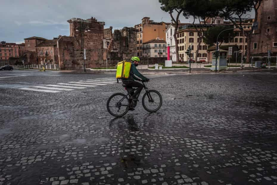 A food delivery man rides a bicycle on Via dei Fori Imperiali during a lockdown imposed by the Italian government in an effort to reduce Covid-19 infections, on 17 March 2021 in Rome, Italy.