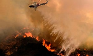 A helicopter drops water to a brush fire at the Holy Fire in Lake Elsinore, California, on Saturday.