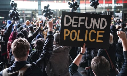 A protester holds a 'Defund Police' sign during a rally for the late George Floyd outside Barclays Center in New York on 14 October.