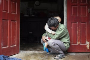 Le Minh Tuan, father of 30-year old Le Van Ha, who is feared to be among the 39 people found dead inside a truck in England, cries while holding Ha's son outside their house in Vietnam's Nghe An province.