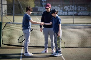 Brothers Henry, 13 and Philippe, 11 shake hands at the end of their tennis match, under the watchful eye of their father Aurelen at Islington Tennis Centre, London