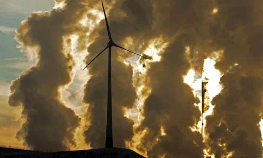 Wind turbine in front of coal power plant