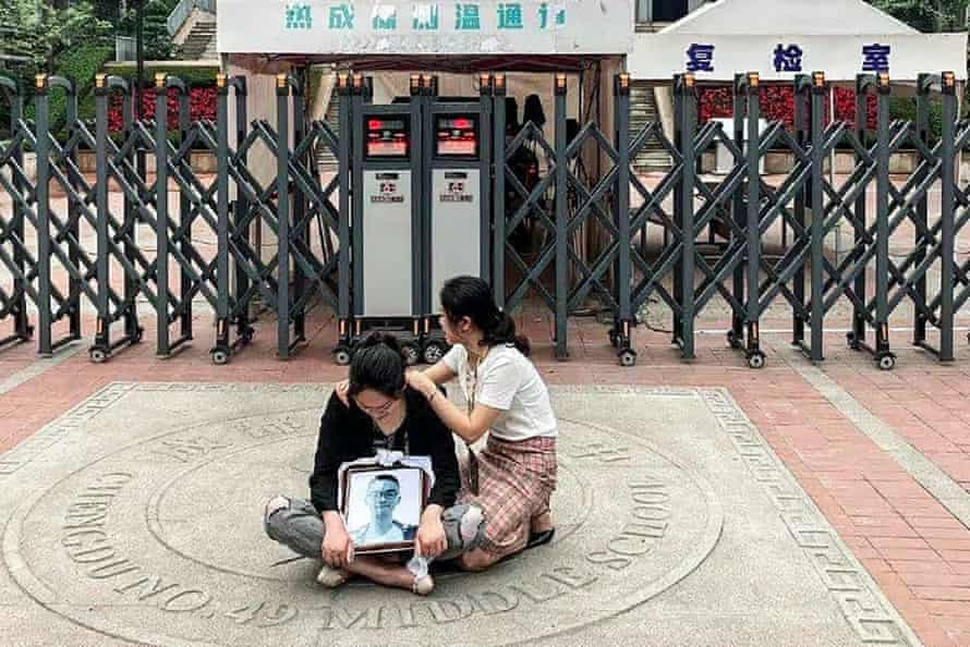 A woman sitting cross-legged on the ground in tears in front some gates, holding a framed picture of a teenager, with another woman consoling her. Chinese characters of the school can be seen displayed above the entrance