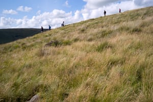 Hikers stroll through the hills near Dovestone reservoir in the north Peak District.