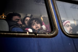 A child looks through a window of a bus following arrival at the port of Mytilene on the island of Lesbos, after being collected at sea by Greek coastguards