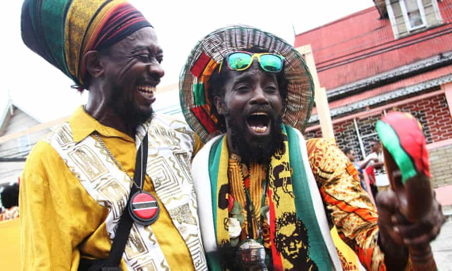 Rapso artist Brother Resistance (left) greets a parade participant during the annual Emancipation Day heritage festival on August 1, 2014 in Port of Spain, Trinidad.