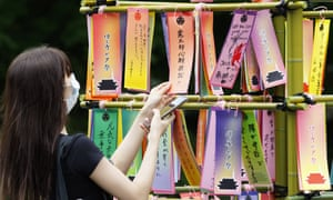 A woman wearing a face mask hangs a wish card on a bamboo branch as part of the Tanabata festival in Zojoji Temple in Tokyo, Japan, 7 July 2020.