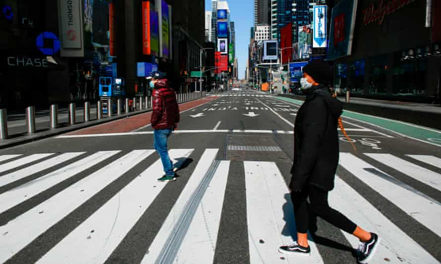 People wear face masks as they cross a street in Times Square in New York City.