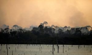A rainforest fire burns near the Jamari River in Itapua do Oeste in Brazil. Photograph: Bruno Kelly/Reuters