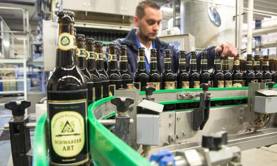 A brewery worker checks bottles of Klosterbrauerei Neuzelle's Schwarzer Abt (Black Abbot) beer.