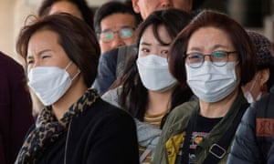 Passengers wear face masks to protect against the spread of the coronavirus as they arrive on a flight from Asia at Los Angeles International Airport.