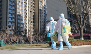 Workers carry a container of coronavirus test samples outside of a residential neighborhood in Shijiazhuang in northern China's Hebei Province