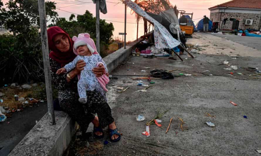 A woman sits with a baby after sleeping rough on a road leading to Mytilene town on the Greek island of Lesbos.