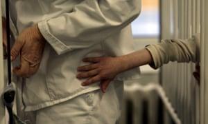 A patient tries to reach a nurse's uniform through cot bars