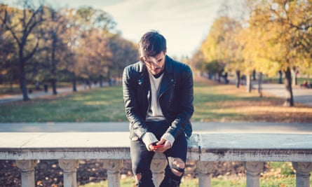 Man alone in the park texting (posed by model)