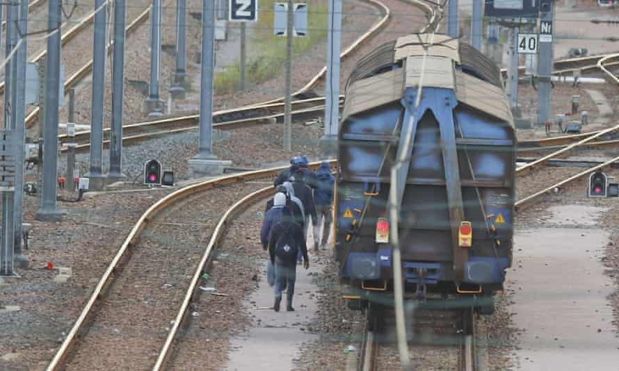 Migrants walk on the tracks in the Eurotunnel site in Coquelles, Calais.