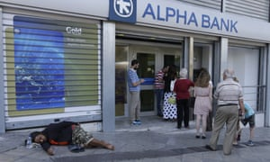 People stand in an ATM queue in Athens.