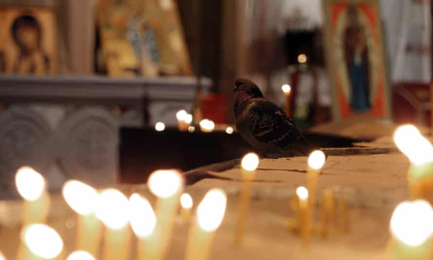 a pigeon among candles at the temple of Saint Sava in Belgrade, Serbia.