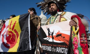 Native American leaders hold signs against drilling in the Arctic refuge outside the Capitol in Washington DC on 11 December.