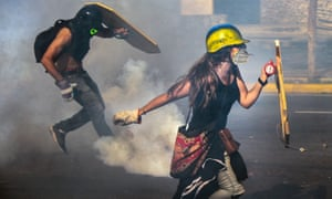Venezuelan opposition activists clash with the riot police in Caracas. Many now wear gas masks and construction helmets.