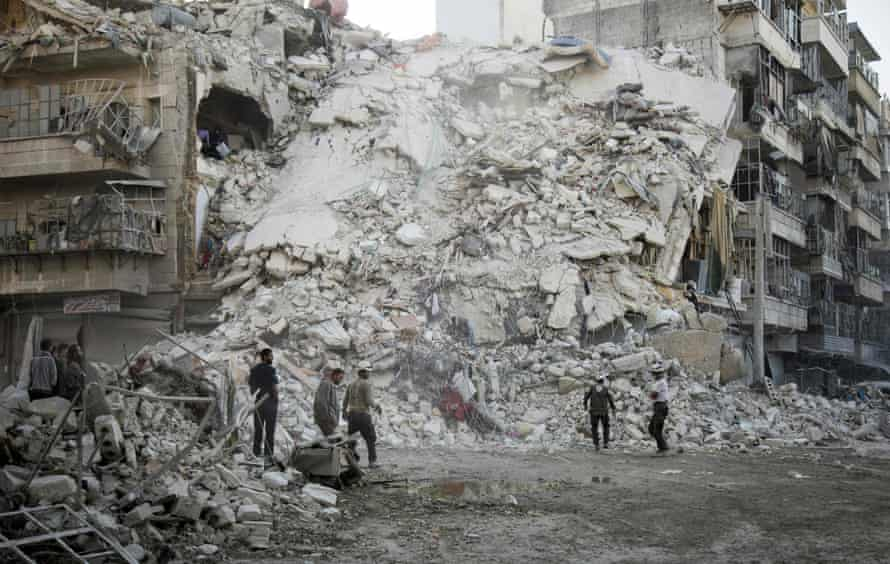 Members of the Syrian Civil Defence, known as the White Helmets, search for victims following airstrikes in Aleppo by Russian and Syrian warplanes.