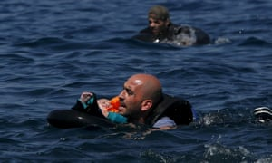 A Syrian refugee holding a baby in a lifetube swims towards the shore after their dinghy deflated 100m off the Greek island of Lesbos at the weekend.