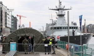 A member of Ireland's National Ambulance Service with members of the defence forces on Sir John Rogerson's Quay in Dublin as defence forces tents have been set up alongside a naval ship ahead of it becoming operational as a testing centre for Covid-19.