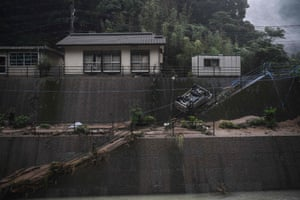 An overturned car in an area hit by torrential rain in Ashikita, in Kumamoto prefecture