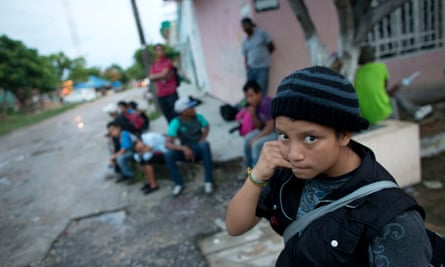 A 14-year-old Guatemalan girl traveling alone waits for a northbound freight train along with other Central American migrants, in 2014.