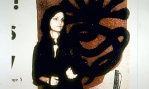 Patty Hearst poses in front of the logo of the Symbionese Liberation Army in 1974.