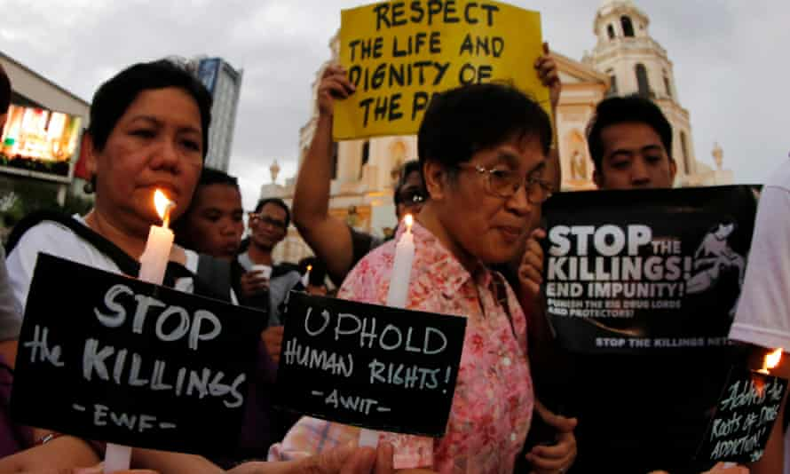 Filipino human rights advocates hold candles and placards during a candle light protest condemning recent extrajudicial killings in Manila, Philippines.