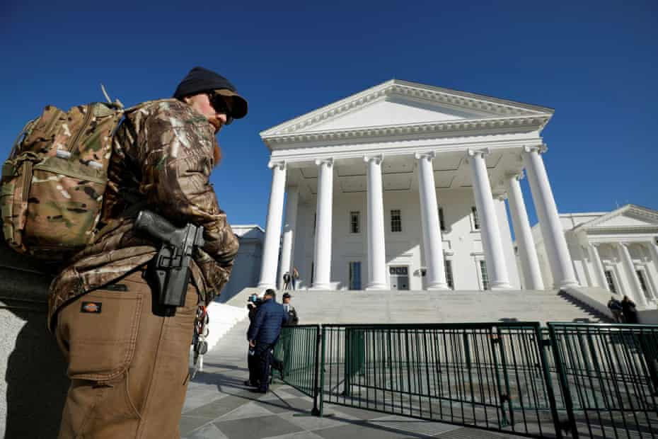 A gun rights activist carries his handgun in a hip holster outside the Virginia state capitol building as the general assembly prepares to convene in Richmond, on 8 January.