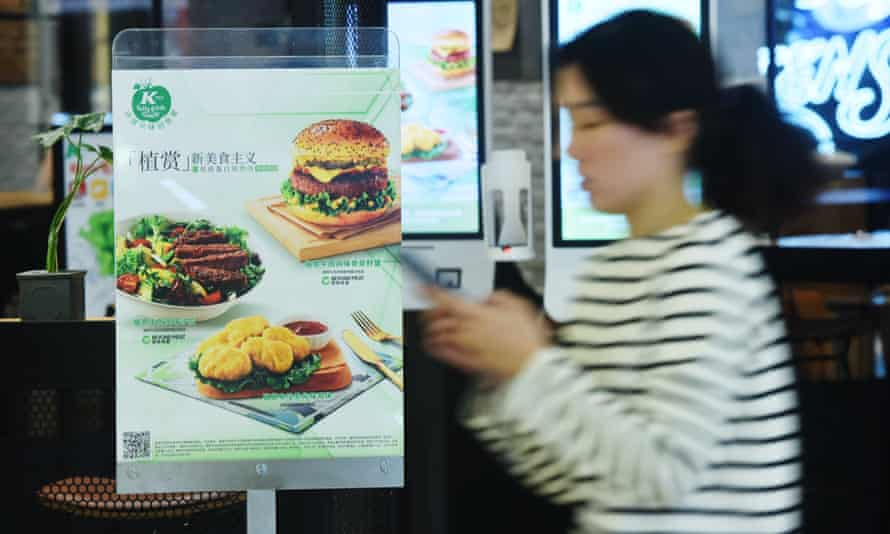A person walks past an advertisement for plant-based products at a KFC store in Hangzhou