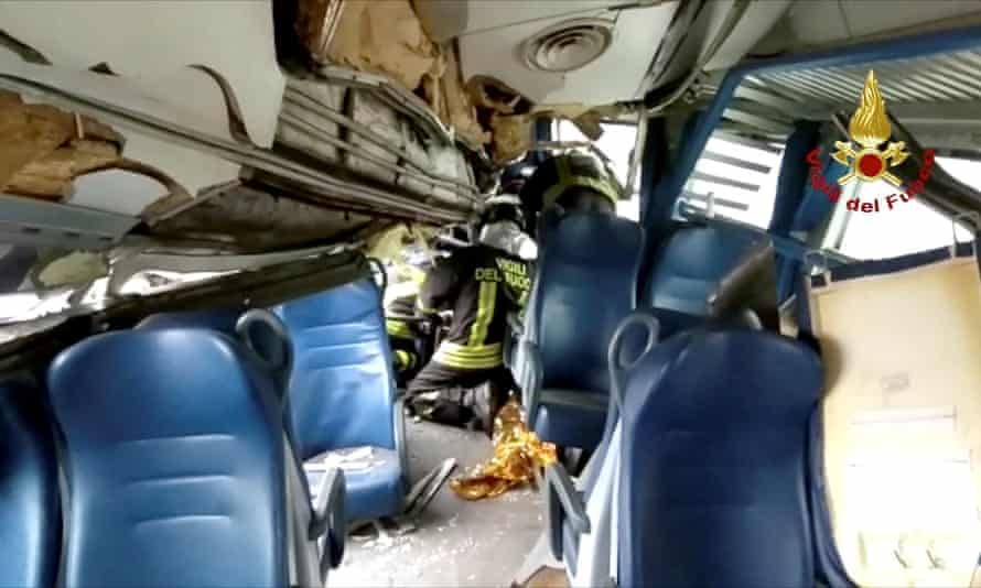 Firefighters inside a derailed carriage.