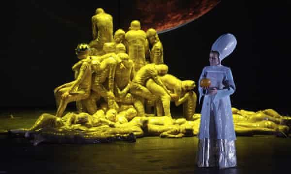 Fricke (Anna Larsson) olha à medida que a pilha de ouro esconde Freia em Carlus Padrissa e La Fura dels Baus produção de Das Rheingold no Palau de les Arts em Valência, Espanha.
