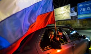 Man holding a Russian flag during the celebrations for the first anniversary of the annexation of Crimea in Sevastopol.
