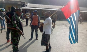 A protester in Fakfak carries the banned Papuan flag