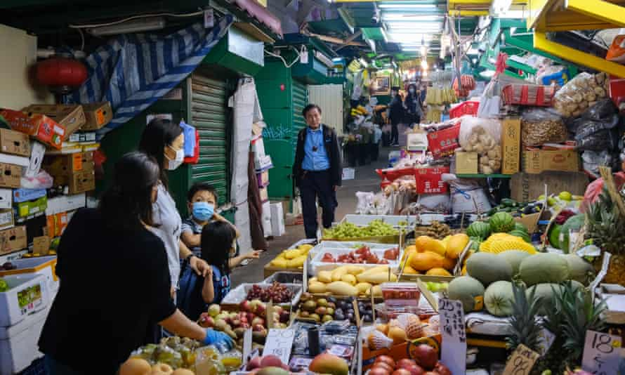 People walk past some fruit stall in Hong Kong.