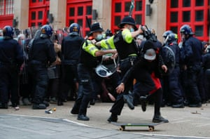 Police officers try to detain a demonstrator.