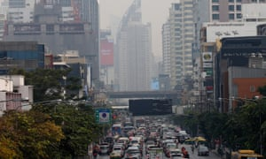 Traffic makes its way along a road as heavy smog lingers in the air in Bangkok