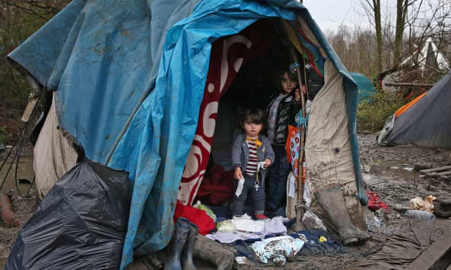 Children stand at the entrance to their shelter in a new migrant camp  in Dunkirk, France