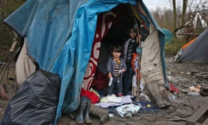 Children stand inside a tent at a refugee camp in northern France