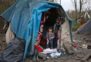 Children stand at the entrance to their shelter in a new refugee camp on 6 January in Dunkirk, France