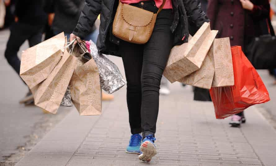 woman walking down street with shopping bags
