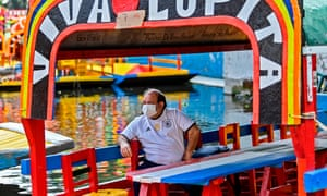 "A man wears a face mask on a ""trajinera"" at the Nativitas canal pier in Xochimilco, Mexico City."