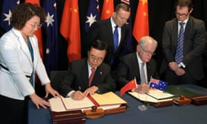 Australian prime minister Tony Abbott, centre, looks on as China's minister of commerce, Gao Hucheng and Australia's trade minister, Andrew Robb, sign the free trade agreement on Wednesday.