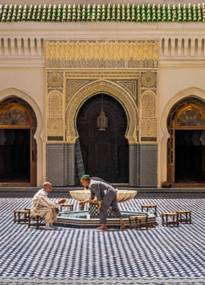 Morocco. Two elderly men bear the unforgiving Moroccan noon heat to find time to sit together and enjoy the cool water of a nearby fountain.